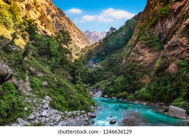 Langtang river in Nepal with human settlement in the background