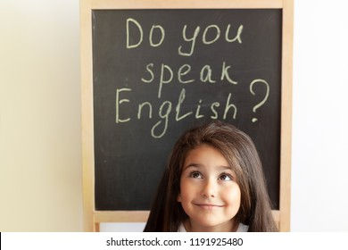 Language education concept.Learn English. Do you speak English. Cute little child girl with blackboard. English language school. English for children.