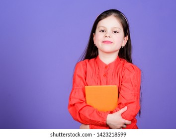 Language and literature textbook for self study. Cute little child holding book in English literature. Adorable small girl enjoy reading literature book. Educational books and literature, copy space.