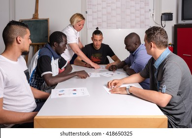 Language training for refugees in a German camp: A female German volunteer is teaching young African (Gambia) and Arabic (Algeria and Tunesia) men the German language in a refugee camp quickly