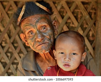 LANGWA, NAGALAND, INDIA - NOV 1, 2017: Old Naga warrior with tribal facial tattoo holds his great-grandson in his hands and poses for the camera in his house, on Nov 1, 2017.