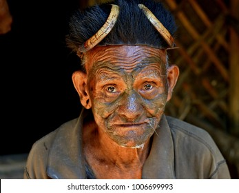 LANGWA, NAGALAND, INDIA - NOV 1, 2017: Old Konyak Naga man with distinctive tribal facial tattoo looks into camera inside his bamboo hut in Langwa village, on Nov 1, 2017.