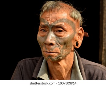LANGWA, NAGALAND, INDIA - NOV 1, 2017: Old retired Indian Konyak Naga warrior and ex-headhunter with distinctive tribal facial tattoo and traditional hairstyle poses for the camera, on Nov 1, 2017.
