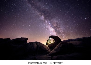Lanscape view of the desert with stars and milky way galaxy over the night sky.  The image depicts astrophotography and nature.