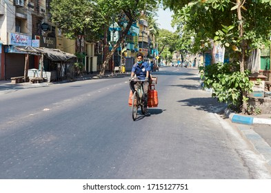 Lansdowne, Kolkata, 04/09/2020: A LPG distribution worker in blue uniform carrying two gas cylinders in his cycle, during lockdown in city. The street is almost empty with no traffic.
