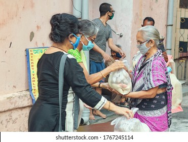 Lansdowne, Kolkata, 05/10/2020: Civic volunteers of a social welfare association giving packaged staples (rice, pulses etc.) to a poor lady during Covid-19 lockdown in Kolkata.