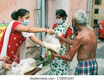 Lansdowne, Kolkata, 05/10/2020: A woman civic volunteers of a social welfare association helping a poor couple by giving them grocery items like rice, pulses etc. during lockdown period in Kolkata.