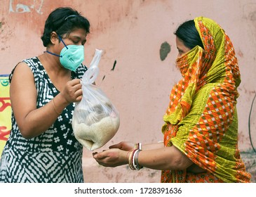 Lansdowne, Kolkata, 05/10/2020: A woman cvic volunteer of a social welfare association helping a poor housewife by giving grocery items like rice, pulses etc. during lockdown period in Kolkata.