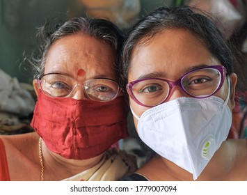 Lansdowne, Kolkata, 07/18/2020: Closeup portrait of simple looking Indian mother and her daughter, both wearing face masks. Concept of home isolation.