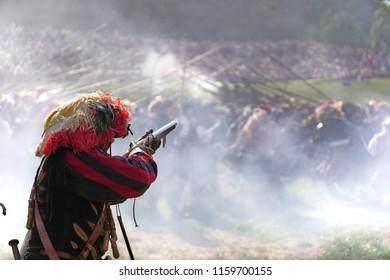 Lansquenet mercenary aiming a flintlock gun in the smoke on the historic battlefield