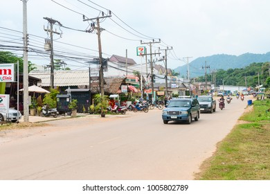 LANTA, KRABI, THAILAND - 17 OCT 2014: Cars and motorbikes on the main Koh Lanta island road with shops and small buildings along
