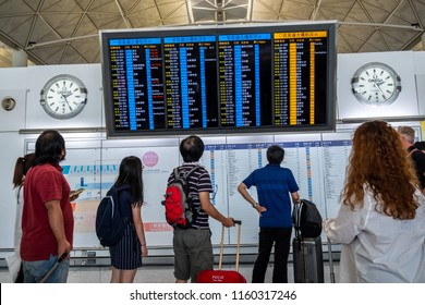 Lantau, Hong Kong  - August 05, 2018 : Airline passengers look at airplanes departure information panel at Hong Kong International Airport