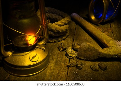 Lantern, axe, gold mining and treasure hood concept.Wood background