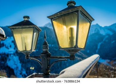 Lantern backlit by the sun with snowy mountains in the background