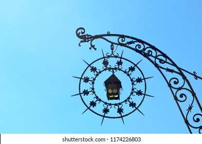 A lantern with coloured panes of glass inside a circular frame hanging from a metal arch. Both are made of iron lattice, with a range of patterns. They are silhouetted against a bright blue sky.