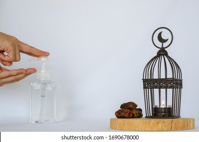 Lantern and dates palm fruit put on wooden tray with a hand pumping alcohol gel in background to protect corona or covid-19 virus for the Muslim feast of the holy month of Ramadan Kareem.
