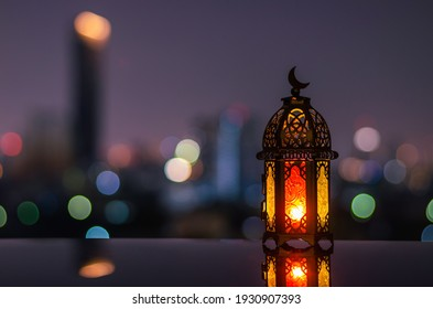Lantern with dusk sky and city bokeh light background for the Muslim feast of the holy month of Ramadan Kareem. - Shutterstock ID 1930907393