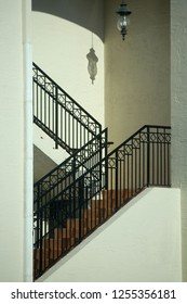 A lantern hanging in a zig-zag stairwell casts a shadow on the wall above the steps. Architectural image
