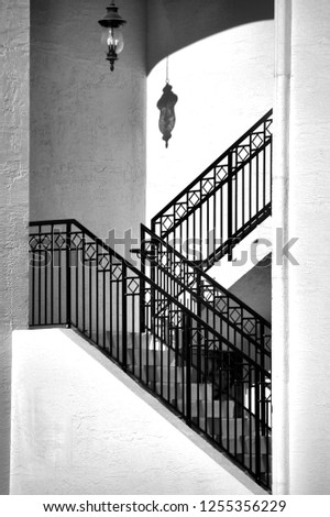A lantern hanging in a zig-zag stairwell casts a shadow on the wall above the steps. Architectural image in black and white.