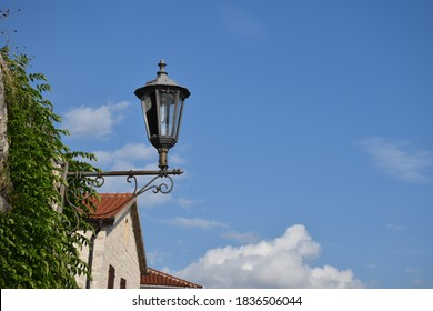Lantern on the wall with leaves on the first plan on the background of the sky with clouds