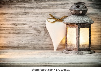 Lantern on a wooden table, a heart symbol.