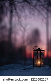 Lantern in snow against defocused sunset forest background.