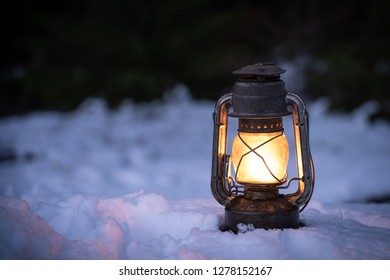 Lantern standing and glowing in the snow at nighttime. Circle of life, rest in peace, love and other symbol concepts.