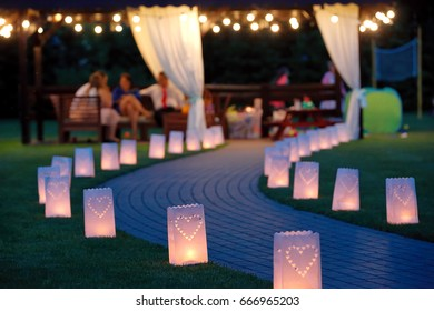 Lantern summerhouse and night lighting path for walks in the garden on blurred background