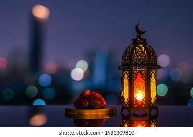 Lantern that have moon symbol on top and small plate of dates fruit with night sky and city bokeh light background for the Muslim feast of the holy month of Ramadan Kareem. - Shutterstock ID 1931309810