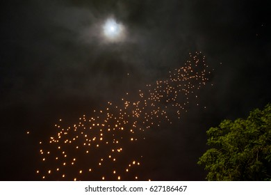lantern-flying before sunrise at Borobudur stupa, plam tree and greenery / Waisak - Vesakha - Vesak celebration, Buddha birth, enlightment and death