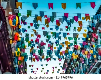 Lanterns, balloons and multicolored paper flags over clear blue sky in june party, Brazil. Streets fully decorated are important part of celebration