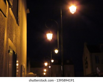 Lanterns with orange light at night against black sky and village house in Arromanches, Normandy, France