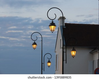 Lanterns with orange light in twilight against blue cloudy sky and white village house in Arromanches, Normandy, France