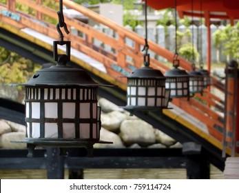 Lanterns in a Row Against a Blurry Bridge in Background at Itsukushima Shrine, Miyajima, Hiroshima Prefecture, Japan