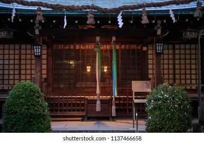 Lanterns shine through wooden lattice doors at small Japanese shrine at dusk