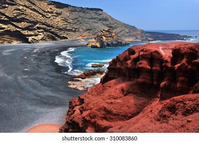 Lanzarote, black sandy beach in gulf of El Golfo, Atlantic ocean near Lago de los Clicos in Canary Islands