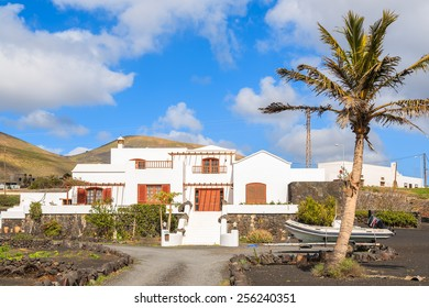 LANZAROTE ISLAND, SPAIN - JAN 17, 2015: typical Canarian house in tropical landscape of Lanzarote island, Spain. Many Europeans buy properties on Canary Islands due to sunny and warm climate.