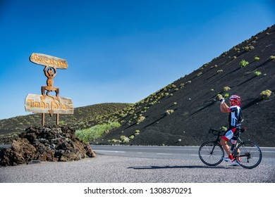 Lanzarote, Spain. Circa February 2019. Cyclist taking a picture of the sign in the entrance of Timanfaya volcanoes park in Lanzarote, Canary Islands