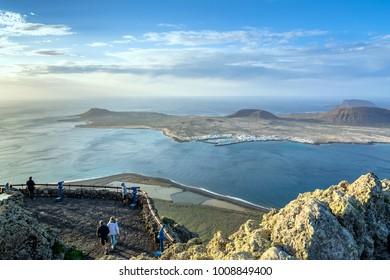 Lanzarote, Spain - December 26, 2016: unidentified tourists look at Atlantic ocean and La Graciosa island at sunset from El Mirador del Rio in Lanzarote. Mirador del Rio was created by Cesar Manrique