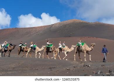 Lanzarote, Spain - October 27, 2018: Tourists on camel tour in Timanfaya National Park, Lanzarote