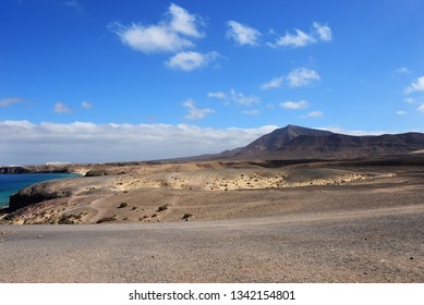 Lanzarote volcanic desert coastline and mountain against the blue cloudy in the background. Lanzarote, Canary Islands, Spain