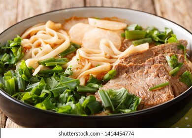 Lanzhou Beef Noodle Soup or Lanzhou Beef Lamian is a type of a very spicy soup of sliced beef, radish, red chili oil and herbs closeup in a bowl. horizontal