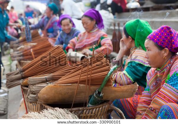 Lao Cai, Vietnam - Oct 17, 2015: Vietnamese Hmong minority women selling incense at Bac Ha traditional weekly flea market.