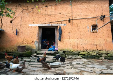 Lao Cai, Vietnam - Sep 7, 2017: Wall thick adobe style house closeup with Ethnic girl embroiders on door at her house with poultry on ground in Y Ty, Bat Xat district