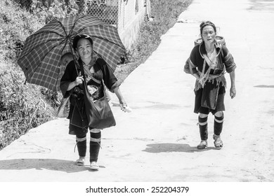 LAO CHAI VILLAGE, VIETNAM - SEP 22, 2014: Unidentified Hmong woman in traditional dress walks in Lao Chai. Hmong is on of the minority eethnic group in Vietnam