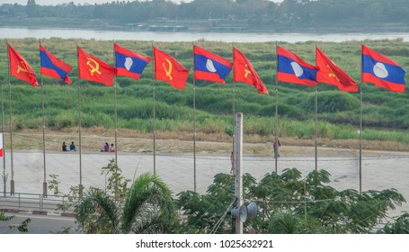 Lao and communist flags flying along the Mekong River in Vientiane Laos