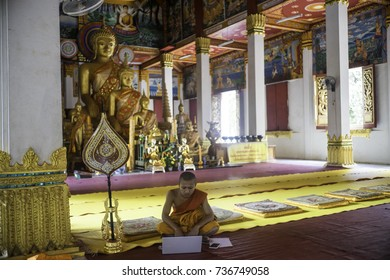 Lao PDR, Vientiane, May 2017, a young Buddhist  monk uses his laptop computer in the temple with Buddha statues looking over his shoulder