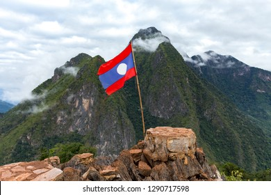 Laos flag on top of Viewpoint of Nong Khiaw - a secret village in Laos. Stunning scenery of limestone cliff valley covered with green rainforest jungle mysterious clouds. A gem of north Laos.