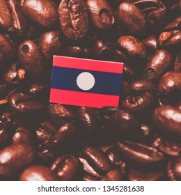 a Laos flag placed over roasted coffee beans
