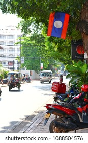 Laos flag at side of the road with traffic on daytime in the central of Vientiane city of Laos on summer season.May 11,2018 : Vientiane,Laos.